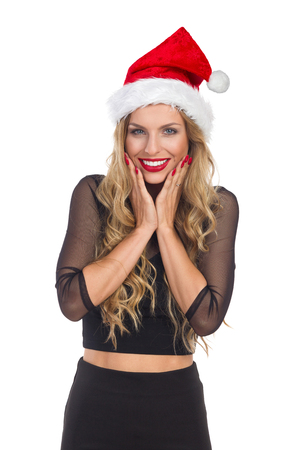 Ecstatic young blond woman in santas hat and black dress holding head in hands and smiling. Waist up studio shot isolated on white.