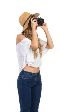 Blond young woman in straw hat, jeans and white shirt talking a photo. Three quarter length studio shot on isolated on white.