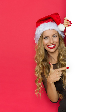 Smiling young blond woman in santas hat and black dress standing behind white placard and pointing. Waist up studio shot on red background.