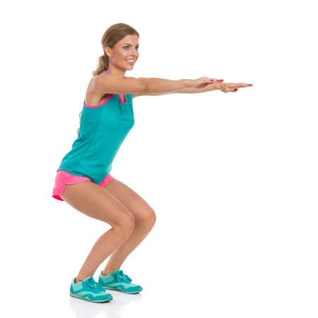 Smiling beautiful young woman in pink shorts, green tank top and sneakers standing with arms outstretched and does a squat, Full length studio shot isolated on white. Stock Photo