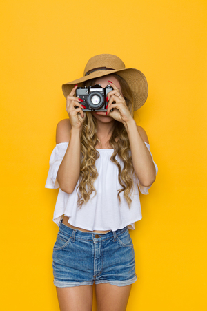 three quarter length: Blond young woman in straw hat, jeans and white shirt talking a photo. Front view. Three quarter length studio shot on yellow background. Stock Photo