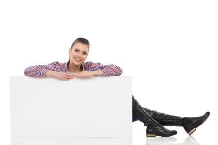 lumberjack shirt: Smiling beautiful young woman in lumberjack shirt and black boots, sitting on floor behind white poster and looking at camera. Full length studio shot isolated on white.
