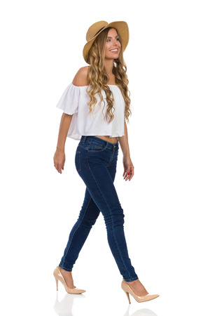 Beautiful smiling blond young woman in straw hat, jeans, white shirt walking and looking away. Full length studio shot on isolated on white. Stock Photo