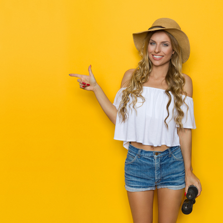 Blond young woman in jeans shorts, white shirt and straw hat holding binoculars, pointing and looking at camera. Three quarter length studio shot on yellow background.