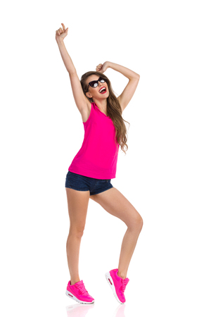cheer full: Happy young woman in sunglasses, pink shirt, jeans shorts and pink sneakers standing legs apart with arms raised and shouting. Full length studio shot isolated on white.