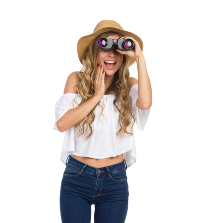 Excited blond young woman in jeans, white shirt and straw hat, looking away through binoculars, Holding hand on chin and shouting. Three quarter length studio shot on isolated on white.