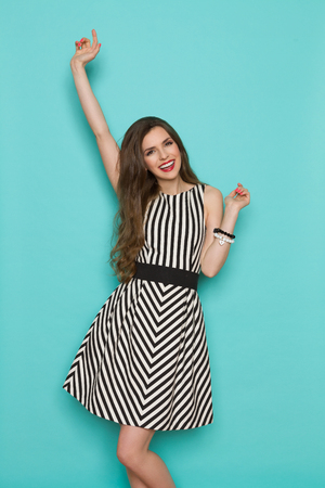 Beautiful girl in black and white striped dress holding arm raised smiling and looking at camera, Three quarter length studio shot on turquoise background.