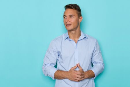 Cheerful handsome young man in blue unbuttoned shirt looking away at copy space. Waist up studio shot on turquoise background.