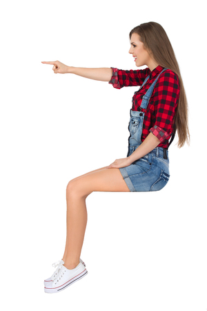 Smiling young woman in red lumberjack shirt, jeans shorts and white sneakers sitting on a top, pointing and looking away. Side view. Full length studio shot isolated on white.