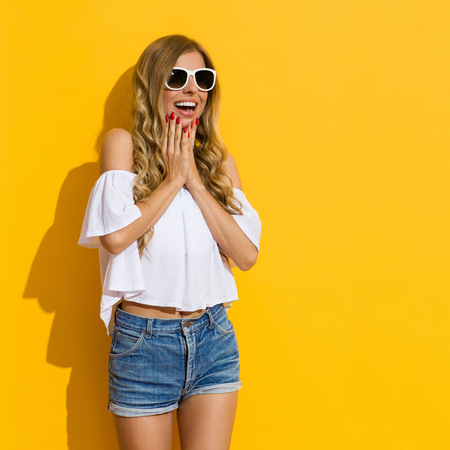 chin on hands: Surprised blond young woman in jeans shorts, white shirt and sunglasses holding hands on chin and looking away, Three quarter length studio shot on yellow background.