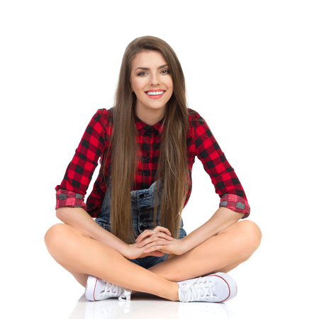 Young smiling woman in red lumberjack shirt, jeans shorts and white sneakers sitting on a floor with legs crossed and looking at camera. Full length studio shot isolated on white. Stock Photo
