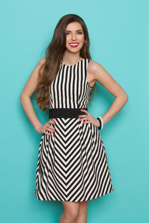 Fashion model in striped dress posing with hands on hip, smiling and looking at camera. Three quarter length studio shot on turquoise background. Stock Photo