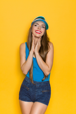 visor: Smiling girl in blue shirt and sun visor holding hands on chin and looking away. Three quarter length studio shot on yellow background.