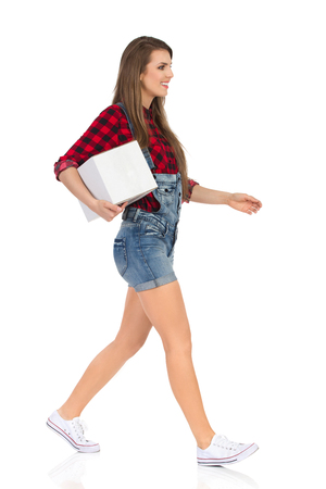 Woman in red lumberjack shirt, jeans dungarees shorts and white sneakers walking, holding white box under the arm and looking away. Side view. Full length studio shot isolated on white. Stock Photo