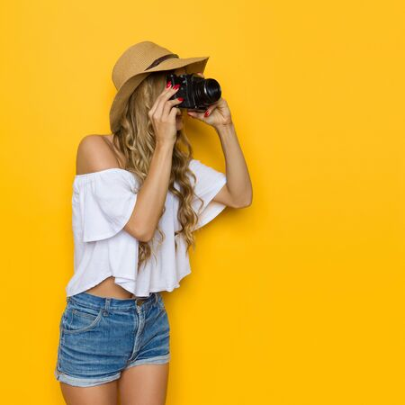 Blond young woman in straw hat, jeans and white shirt talking a photo. Side view. Three quarter length studio shot on yellow background.