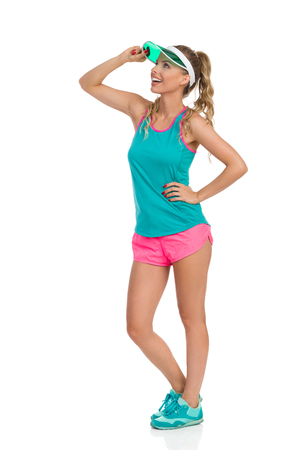 visor: Smiling beautiful young woman in pink shorts, green tank top, sun visor and sneakers, standing with hand on hip and looking away, Side view. Full length studio shot isolated on white.