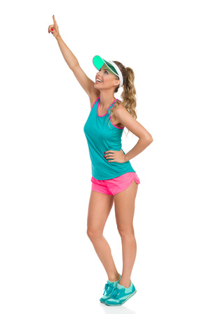visor: Smiling beautiful young woman in pink shorts, green tank top, sun visor and sneakers, standing tip toe looking up and pointing, Side view. Full length studio shot isolated on white.