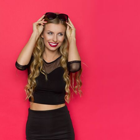 Beautiful smiling blond young woman in elegant black dress holding sunglasses on head and looking away. Waist up studio shot on red background. Stock Photo