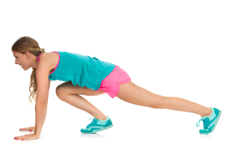 Woman in vibrant sports clothes doing a mountain climber exercise. Side view. Full length studio shot isolated on white.