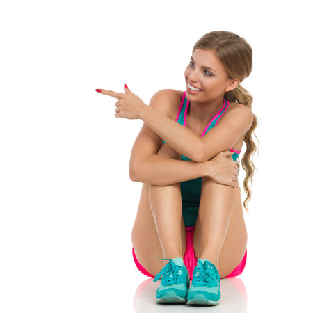 isolated sign: Beautiful smiling young woman in pink shorts, turquoise tank top and sneakers sitting on a floor, looking away and pointing. Front view. Full length studio shot isolated on white.