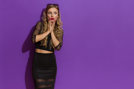 chin on hands: Surprised beautiful blond young woman in elegant black dress holding hands on chin and looking away. Three quarter length studio shot on yellow background.