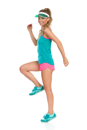Happy beautiful young woman in pink shorts, green tank top, sneakers and green sun visor standing tiptoe on one leg and looking at camera, Side view. Full length studio shot isolated on white.