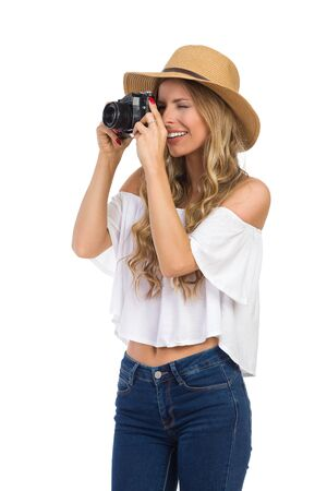 Smiling blond young woman in straw hat, jeans and white shirt taking a photo. Three quarter length length studio shot isolated on white. Stock Photo