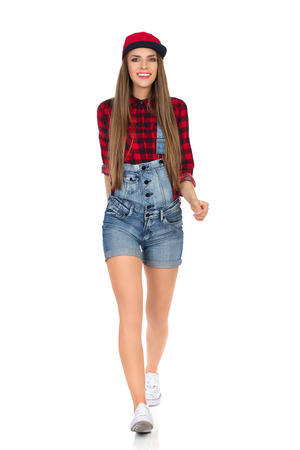 towards: Woman in red lumberjack shirt, jeans shorts, white sneakers and full cap walking towards camera and smiling. Full length studio shot isolated on white. Stock Photo