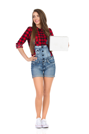 dungarees: Smiling young woman in red lumberjack shirt and jeans dungarees shorts holding white cardboard box and looking away. Full length studio shot isolated on white.