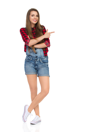 Smiling young woman in red lumberjack shirt, jeans dungarees shorts and white sneakers standing with legs crossed, pointing and looking at camera. Full length studio shot isolated on white.