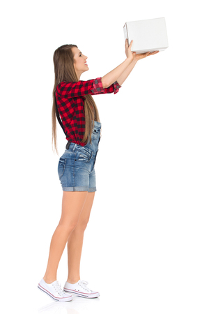dungarees: Smiling young woman in red lumberjack shirt and jeans dungarees shorts holds white cardboard box. Full length studio shot isolated on white. Stock Photo