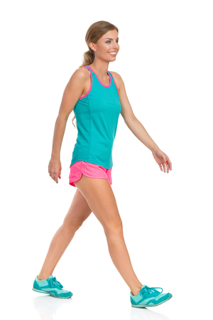 Smiling beautiful young woman in pink shorts turquoise tank top and sneakers walking and looking away, Side view. Full length studio shot isolated on white.