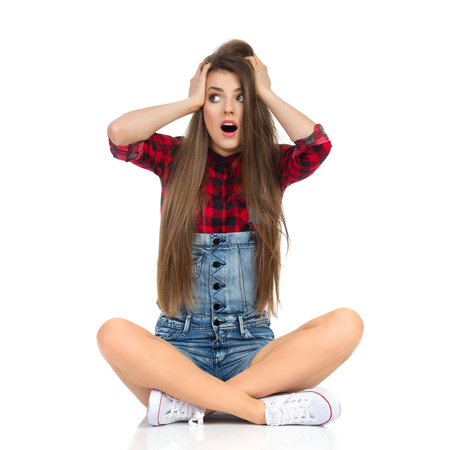 Worried young woman in red lumberjack shirt, jeans shorts and white sneakers sitting on a floor holding head in hands and looking away. Full length studio shot isolated on white.