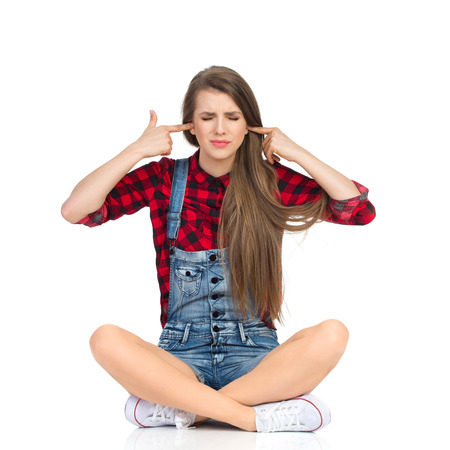 Disgusted young woman in red lumberjack shirt, jeans shorts and white sneakers sitting on a floor with legs crossed, closes eyes and holds fingers in her ears . Full length studio shot isolated on white. Stock Photo