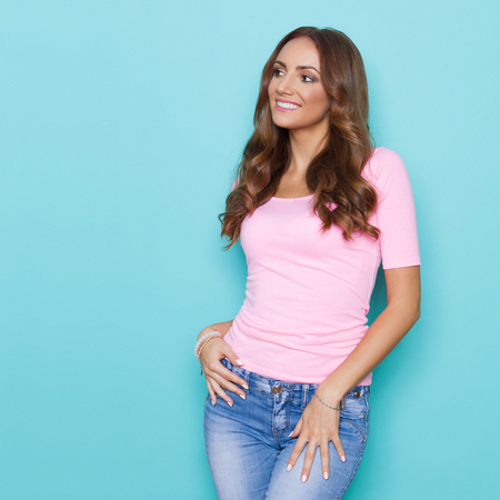 Beautiful young woman in pink shirt and jeans looking away and smiling. Three quarter length studio shot on turquoise background.
