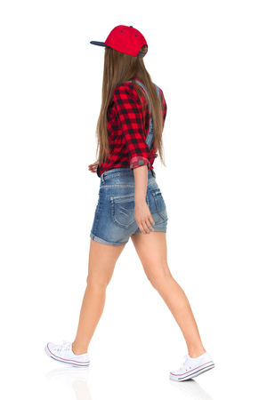 Woman in red lumberjack shirt, jeans shorts white sneakers and full cap walking. Rear side view. Full length studio shot isolated on white.