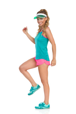 visor: Smiling beautiful young woman in pink shorts, green tank top, sun visor and sneakers standing on one leg and looking at camera. Side view. Full length studio shot isolated on white. Stock Photo