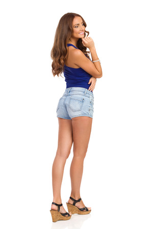 Smiling girl in blue shirt, jeans shorts and cork heels standing, holding hand on chin and looking away. Rear view. Full length studio shot isolated on white.