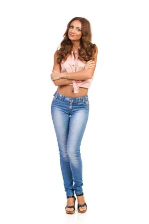 Attractive young woman in pink shirt, jeans and cork high heels standing with arms crossed and looking at camera. Full length studio shot isolated on white.