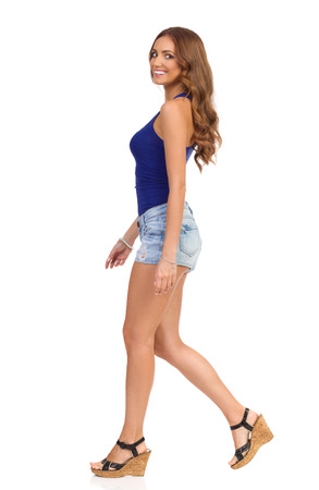 Young smiling woman in blue shirt, jeans shorts and cork heels walking and looking at camera. Full length studio shot isolated on white. Stock Photo