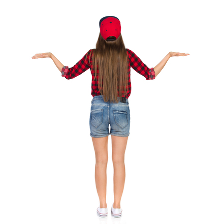 dungarees: Woman in red lumberjack shirt, jeans dungarees shorts, white sneakers and red cap standing with hands raised and presenting something. Rear view. Full length studio shot isolated on white.