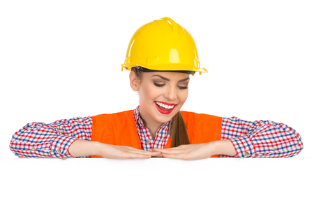 reflective vest: Smiling beautiful young woman in yellow hardhat, orange reflective vest and lumberjack shirt leans on a banner, and looking down on a white copy space. Head and shoulders studio shot isolated on white. Stock Photo