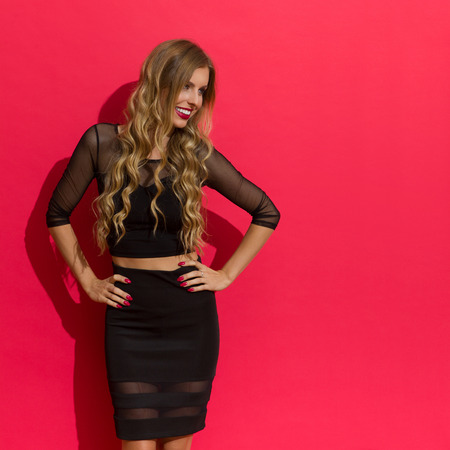 Beautiful blond young woman in elegant black dress posing with hands on hip, smiling and looking away. Three quarter length studio shot on red background.