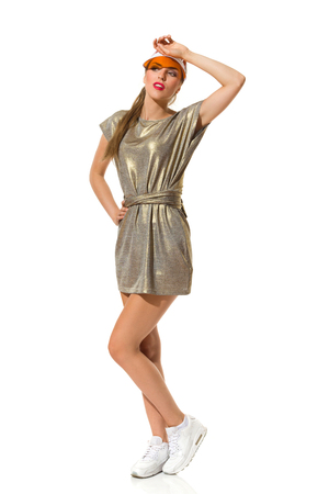 Young beautiful woman in gold mini dress, sneakers and orange plastic cap posing with hand on forehead. Full length studio shot isolated on white.