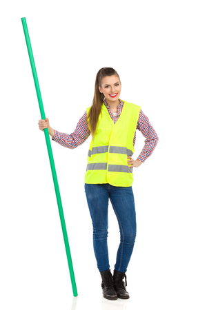 Young woman in yellow reflective vest, jeans, and lumberjack shirt posing with hand on hip and holding chroma key stick. Full length studio shot isolated on white.