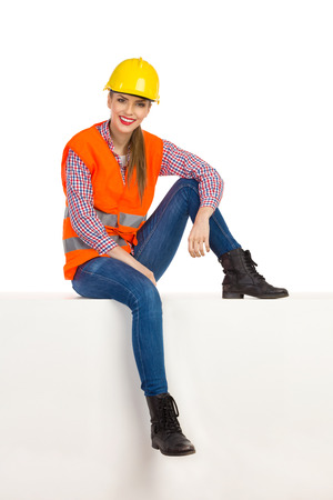 reflective vest: Cheerful young woman in yellow hardhat, orange reflective vest, lumberjack shirt, jeans and black boots, sitting relaxed on top on white box and looking at camera. Full length studio shot isolated on white.