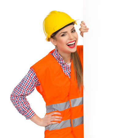 reflective vest: Amused young woman in yellow hardhat, orange reflective vest and lumberjack shirt standing behind big white banner, holding it and looking at camera. Waist up studio shot isolated on white.