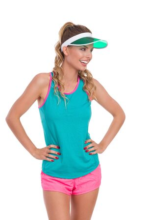 visor: Smiling beautiful young woman in pink shorts, green tank top and sun visor holding hands on hip and looking away, Front view. Three quarter length studio shot isolated.
