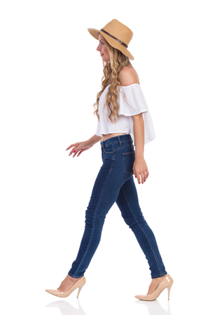 Blond young woman in straw hat, jeans, white shirt walking and looking away. Side view. Full length studio shot isolated on white.