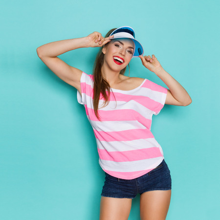 visor: Smiling carefree beautiful young woman in pink striped shirt, blue sun visor and jeans shorts. Three quarter length studio shot on turquoise background.